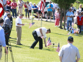 Image of a memorial Day program at the cemetery. Veterans are placing flags for deceased veterans.